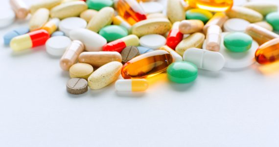 Vitamins, omega 3, cod-liver oil, dietary supplement and tablets an embankment on a light background close up, the top view